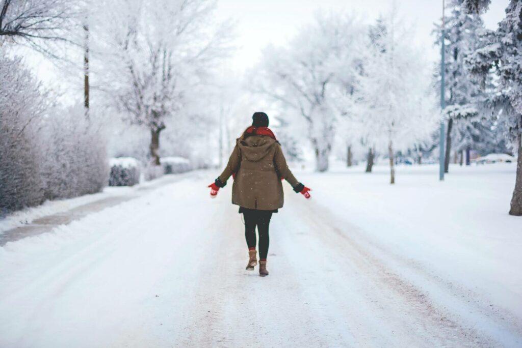 nainen kävelee talvisessa maisemassa