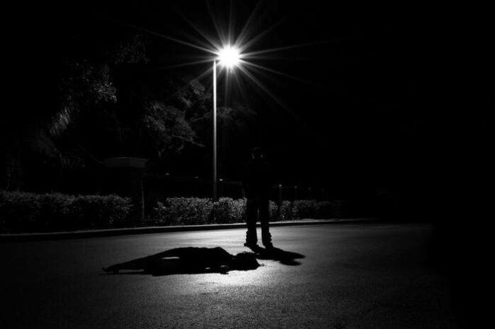 pimeä maisema jossa maassa makaavan uhrin vierellä seisoo synkkä hahmo