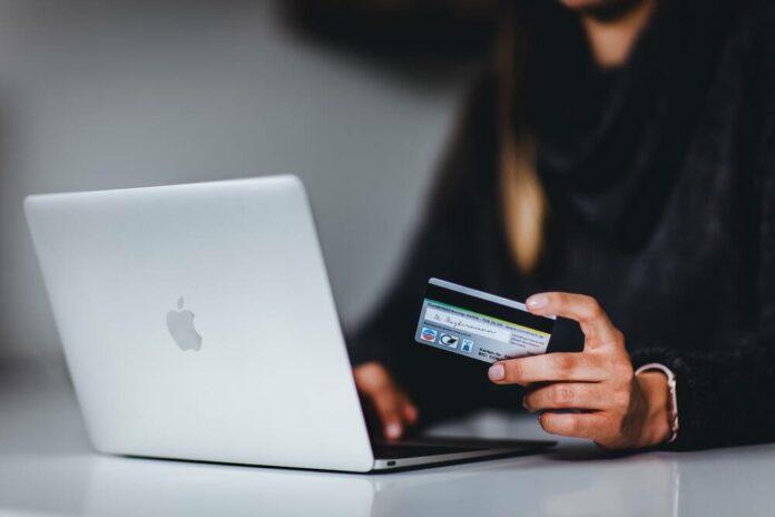 nainen maksaa nettiostoksia pankkikortilla