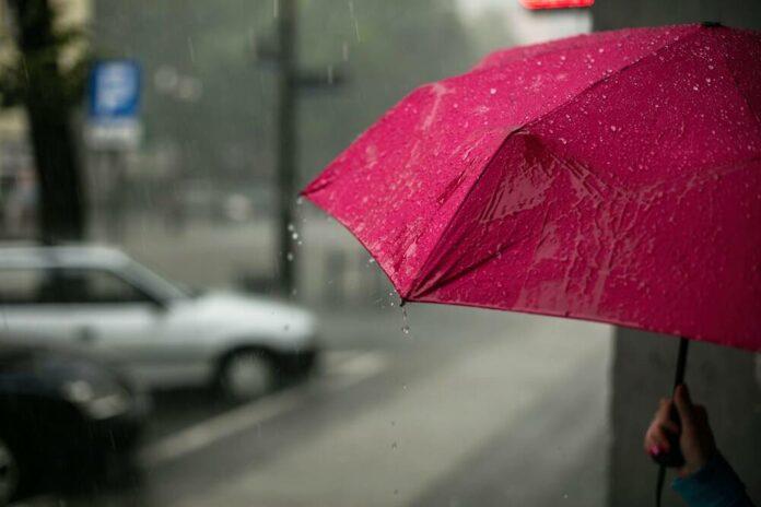 Punainen sateenvarjo harmaan sateisessa säässä