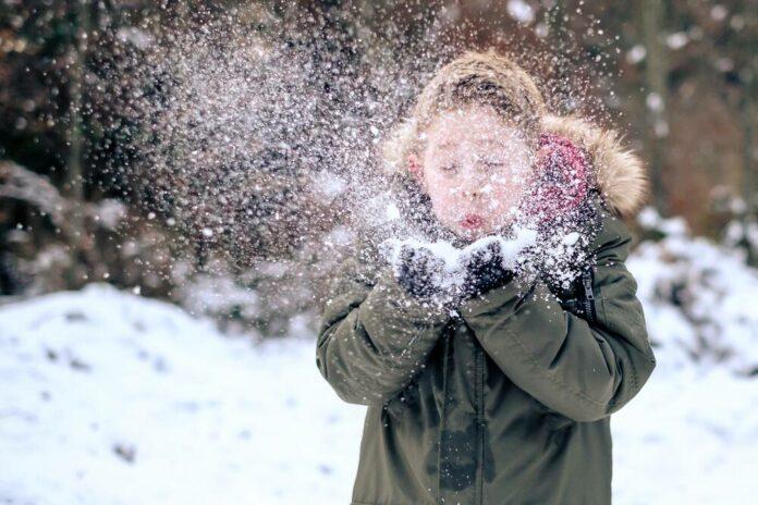 Lapsi puhaltaa käsistään lunta